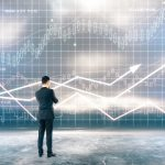 Research concept with businessman standing in front of digital business chart